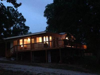 Night time view of house, decking, and exterior lighting.