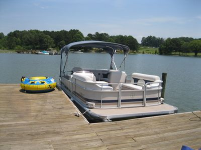 22 ft pontoon boat docked at home available for rent with tube and tow rope.