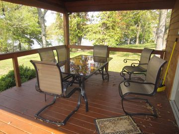 The covered deck area/ table with the beautiful lake view behind it.