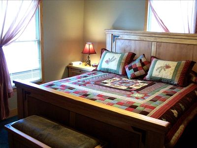 The master bedroom has a rustic king-sized bed with a warm, cozy quilt