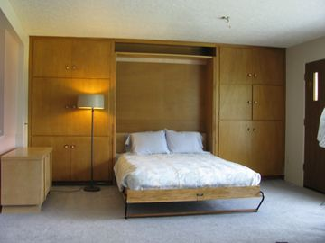 The new oak Murphy bed folds out from the original built-ins.