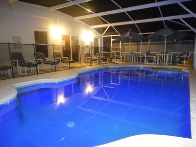 Color changing swimming pool and spa and patio seating area (night view)