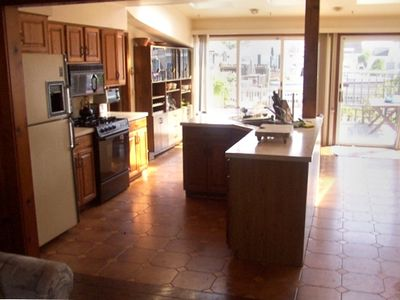 INSIDE KITCHEN W/ ISLAND, TILE FLOORS, SLIDERS TO DECK