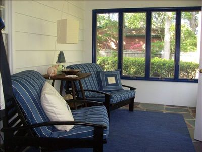 Blue, sunny and breezy entry/sitting room looks out to garden and lake