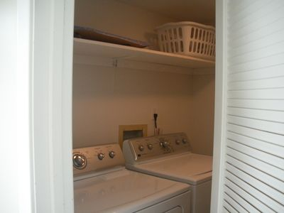 Laundry room with full size washer/dryer and mini fridge behind the door
