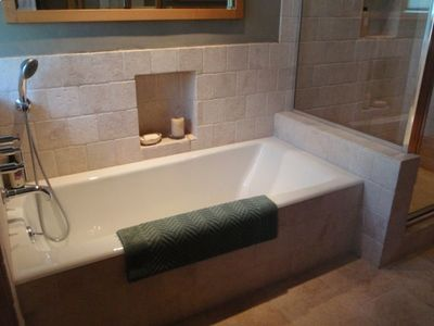 Luxurious Bathroom. Travertine stonework, spacious tub and two person shower