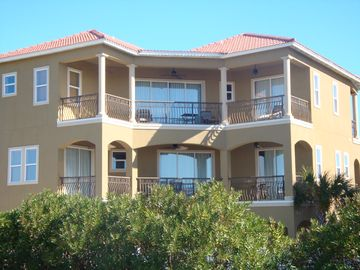 View of rear of house with large balconies looking down over the pool area