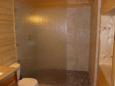 Luxurious glass-walled shower w/ pebbled flooring