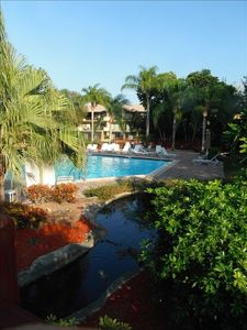 Tropical landscape pool on island located in center of living community.
