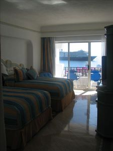 Bedroom with 2 double beds. Perfect view of a cruise ship anchoring in the bay.