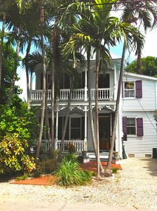 Beautiful palm shaded front of this classic Key West house