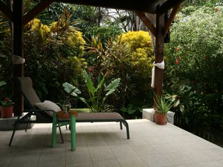 Montezuma villa photo - The downstairs terrace is surrounded by colorful foliage.