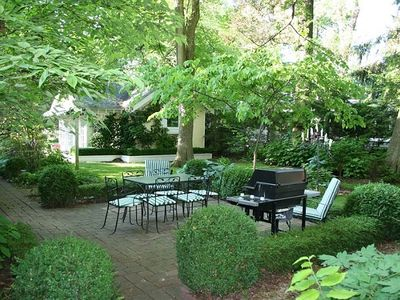 Patio area with table and gas grill surrounded by beautiful gardens!