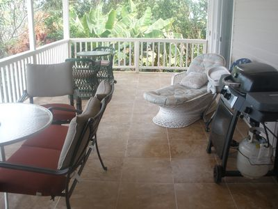 Large west lanai with gas grill, seating for drinks and dining.