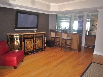 Huge Lower level tv entertaining room with wet bar along far wall
