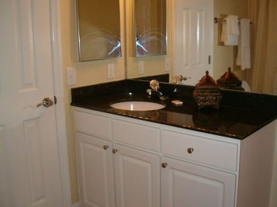 The large bathroom features granite countertops