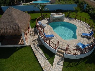 Deck around the private pool with lounge chairs and a large palapa roofed patio.