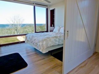 Chilmark house photo - Bedroom #5 - Queen Bed. Sliding Barn Door, Floor-To-Ceiling Windows, Water Views, Mahogany Built-ins