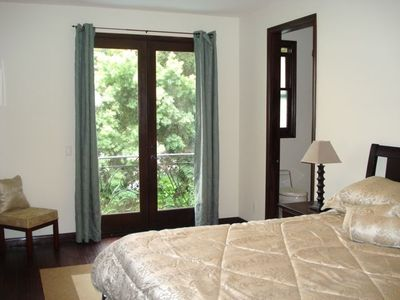 Bedroom 3- Queen Bed with View of Trees and Pool