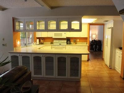 Spacious kitchen area with stove, refrig, microwave, dishwasher & wine rack.