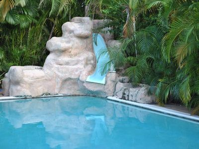 Waterfall with slide and large pool with huge patio.