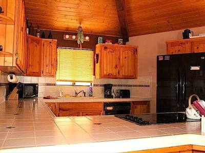 Country kitchen with a large breakfast bar and door to the deck.  Fully stocked!