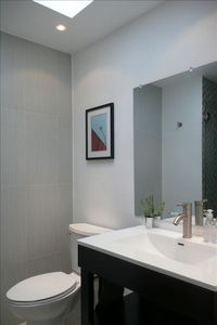 Hallway Bathroom has a walk in shower with glass mosaic tiles