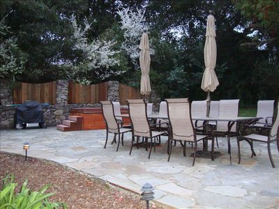 Backyard terrace with seating for up to 12, hot tub, gas bbq grill, and lawn
