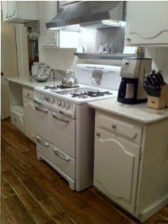 Fully stocked kitchen with restored Wedgewood gas stove and granite countertops