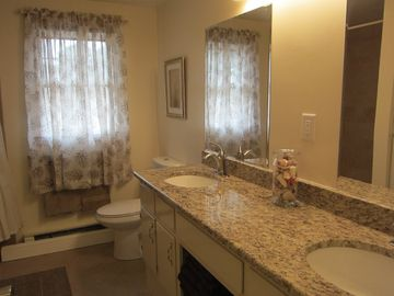 Bath with double bowl sink, large tile tub/shower to left just out of photo.