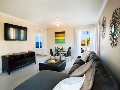 "Ocean view living room with 52"" flat scrren TV and seating for 5 guests."