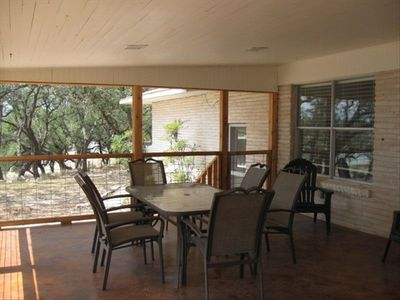 Large outside dining table on covered porch with lakeview.