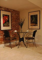 Capitol Hill studio photo - Bistro style dining nook with exposed brick and Parisian posters.