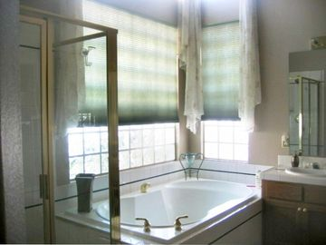 Master bathroom with Roman tub, shower, two sinks and private toilet area.