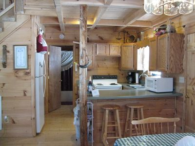 cabin kitchen from dining area. stove w oven, microwave, coffee pot and refrig.