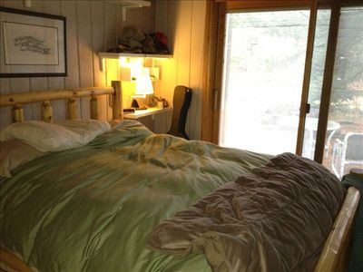Higgins Lake house rental - Master bedroom with eight-foot custom door wall looking onto the river.