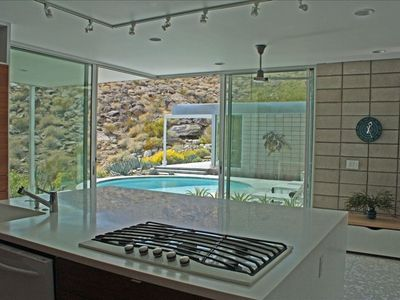 Kitchen opens up to poolside patios & mountain views.