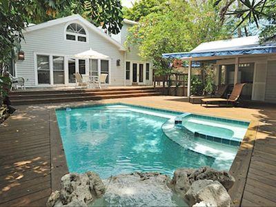 Swimming pool, large deck, pool cabana to the right and house in the back