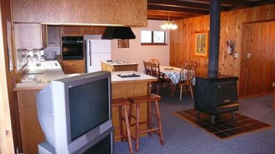 open kitchen, dining, wood stove.  living area facing TV