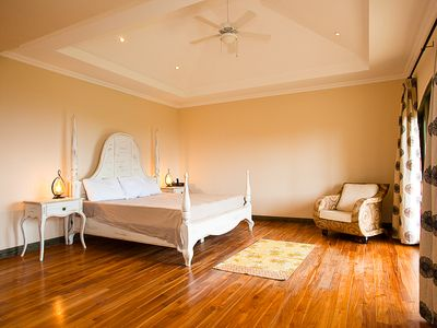 The master bedroom with ceiling fan and warm toned wood floors.