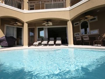 Private pool with lounge chairs, dining table with chairs and gas grill