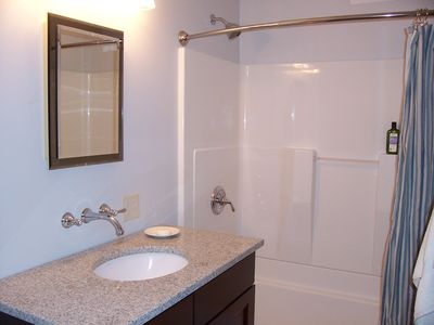 Hall bathroom with tub/shower combination, cherry vanity, and granite counter.