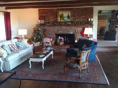 Ranch living room decorated for Christmas with a peak into the family room