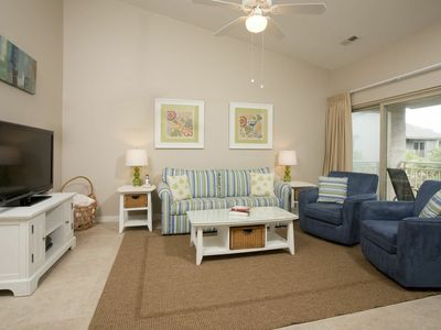 The living room is bright, spacious, comfortable and includes HDTV.