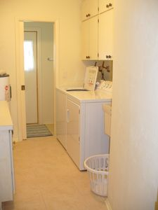 Laundry room, adjacent half-bath opens to outside.