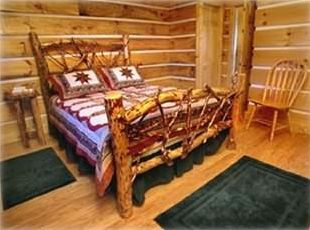 The cabin's all-wood interior includes a handcrafted log bed in the cozy bedroom