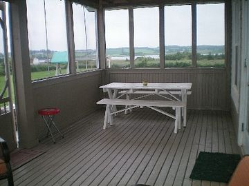 Outdoor eating area in the screened in porch, dine al fresco anytime!