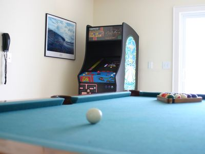 Pool Table with arcade games in the background
