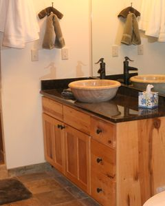 Bathroom has granite counters, basin sink, and oversized, doubled headed shower.