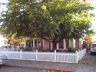 Storybook looks with white picket fence, wrap-around porch and giant shade tree.